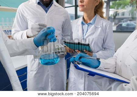 Scientist Hand Holding Flask And Group Of Researchers Make Notes Of Research In Laboratory, Scientific Workers Analyzing Experiment In Lab