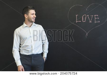 A man in a suit against a blackboard looks at a chalk drawn heart.Smiling