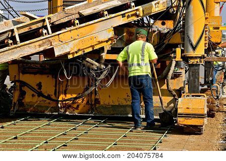 An unidentified man operating the machine used to lay concrete to form a new sidewalk or highway.