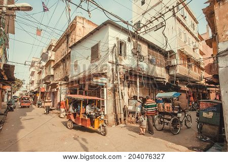 JAIPUR, INDIA - JAN 22, 2017: Local shops rickshaw and walking people on crossroad of historical indian city on January 22, 2017. Jaipur with population 6664000 people is a capital of Rajasthan