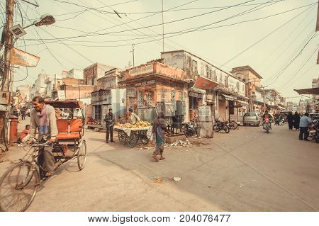 JAIPUR, INDIA - JAN 22, 2017: Street life with local food vendors vehicles and poor houses of historical indian city on January 22, 2017. Jaipur with population 6664000 people is a capital of Rajasthan