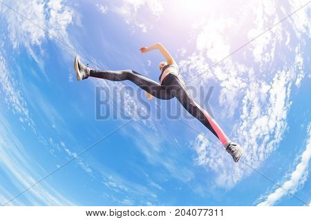 Low angle view of athlete remaining stationary in air while jumping or running against cloudy sky background