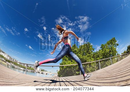Side view portrait of sportswoman running and sprinting outdoors in downtown