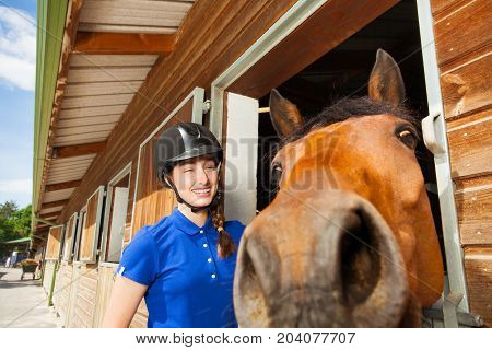 Portrait of laughing jockey girl standing by training stable with her funny horse looking at camera