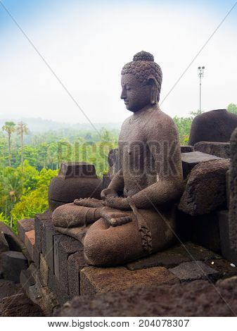 JOGJA, INDONESIA - AUGUST 12, 2O17: Close up of buddha statue and stupa at Borobudur Buddhist temple Candi Borobudur . Built in 9th century, cataloged as UNESCO World Heritage Site. Central Java, Indonesia.