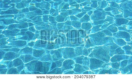 Blue water surface in swimming pool. Ceramic tiles on the bottom of the pool.
