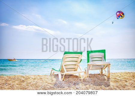 Two chaise lounges on sea beach. Sun beds on sea. Parasailing with boat over sea. Relax vacation on tropical resort beach.