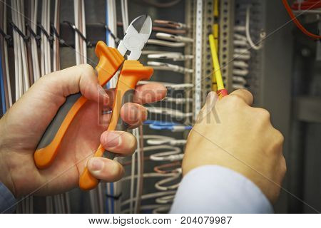 Cutters and screwdriver in hands of electrician close-up against background of electrical terminal block
