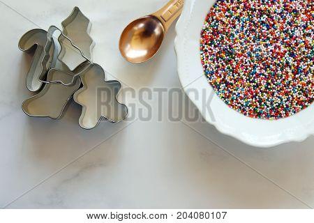 Metal cookie cutters, teaspoon and bowl of rainbow sprinkles. White marble copy space.