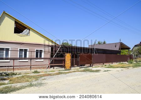 Brick House With A Fence And Gates. View Of A New Built-up Fence And A House Made Of Bricks And Corr