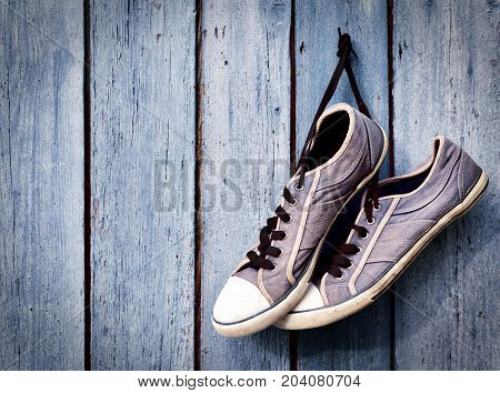 a pair of old man's dirty blue sneakers hanging on a wooden wall empty space