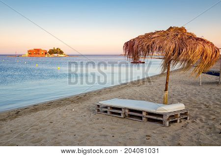 A beautiful remote corner of paradise. Turquoise sea a deckbed gold sand and umbrella. Marzamemi Sicily Italy