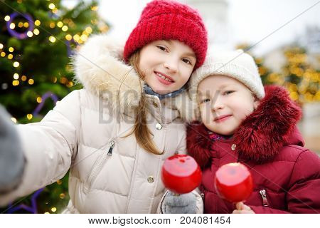 Two Adorable Little Sisters Eating Red Apples Covered With Sugar Icing On Traditional Christmas Mark