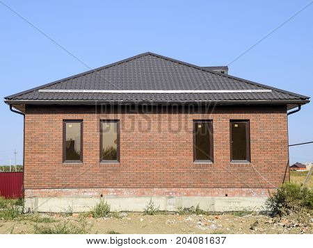 The House With Plastic Windows And A Roof Of Corrugated Sheet. Brown Roof And Brown Brick