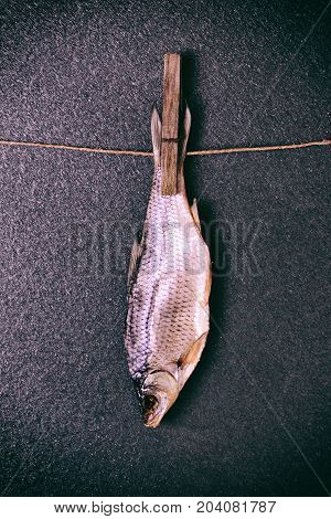 dried salted fish suspended from the tail on a rope with a wooden clothespin