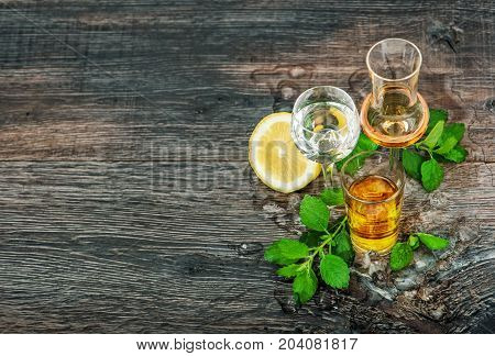 Drinks with ice lemon mint leaves on wooden background. Aperitif whiskey gin rum vodka