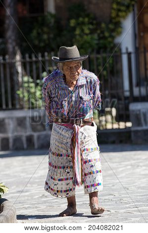 January 1 2015 San Pedro la Laguna Guatemala: elderly mayan man in traditional wear walking barefoot in the centre of the town