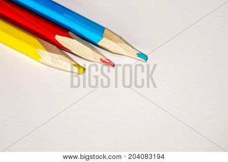 Red, yellow and blue crayons and white paper sheet on the desk