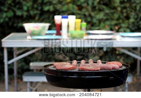 Sausages And Burgers Sizzling On A Barbecue, With A Camping Table In The Blurred Out Of Focus Backgr