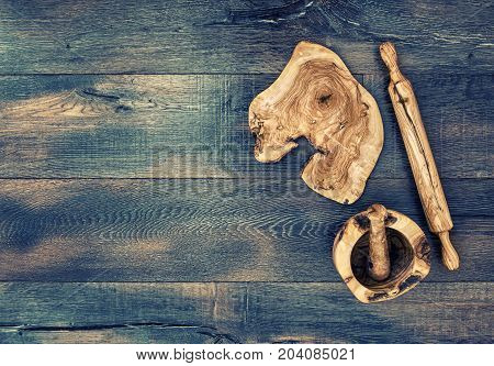 Kitchen utensils. Rolling pin mortar and wooden board on rustic background. Vintage style toned picture