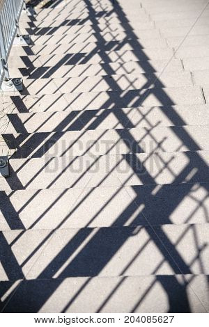 The close up of a walkway and a staircase whose balustrade balances symmetrical shadows.