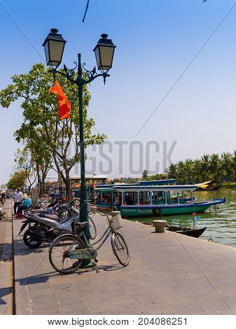 HOIAN, VIETNAM, SEPTEMBER, 04 2017: Bikes and motorcycles parked in a row, and some boats ofr tourist in the water in Hoi An ancient town, UNESCO world heritage.