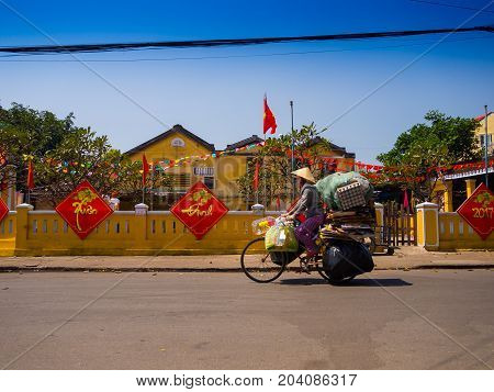 HOIAN, VIETNAM, SEPTEMBER, 04 2017: Unidentified woman biking in the street view with old houses, and colorful lanters made of paper, in Hoi An ancient town, UNESCO world heritage. Hoi An is one of the most popular destinations in Vietnam.