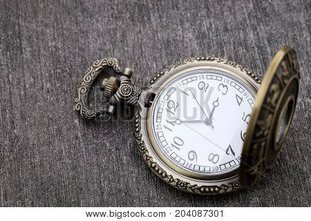 Old pocket watch on dark gray table background