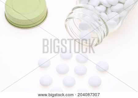 Glass bottle and pills on white background