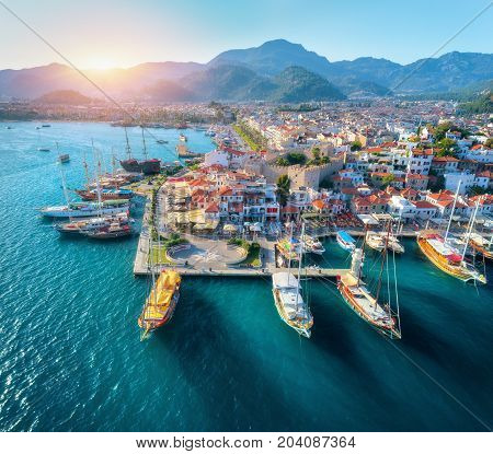 Aerial view of boats and beautiful architecture at sunset in Marmaris, Turkey. Colorful landscape with boats in marina bay, sea, city, mountains. Top view from drone of harbor with yacht and sailboat