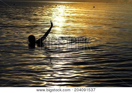 Woman swimming with bikini silhouette on Thung Wua Lan Beach at Chumphon Province Thailand.
