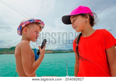 Cute Kids On A Boat Trip. Boy Is Playing A Toy Guitar And Sings For His Beautiful Girlfriend.