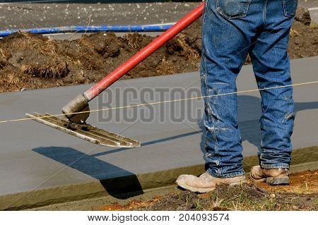 Construction worker ready to use a bull float on the edge of freshly poured concrete on a sidewalk project
