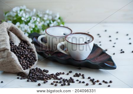 Two cups of freshly brewed, frothy cappuccino. Spilled coffee grains, chocolate and cane sugar. Theme of coffee, cappuccino, mocha chino, america no. Beautiful elegant background with place for text