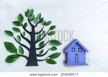 beautiful fantasy symbolic tree and a toy house. Symbol of peace and family. Environment, forest restoration, ecosystem, ecology. Background with space for text