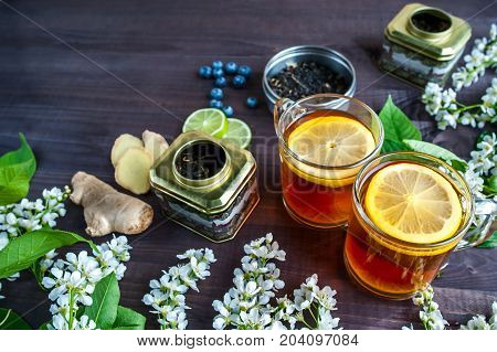 Theme of tea, background with space for text, dark. Black tea in transparent mugs with lemon, ginger, lemons, limes, mint, cherry blossoms. Food industry, tea packing, restaurant business