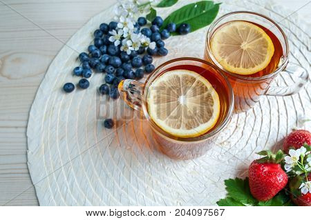 Tea background . Tea in transparent mugs with lemon, lemons, limes, mint, cherry blossoms. Stylish, colorful background. Food industry, tea packing, restaurant business