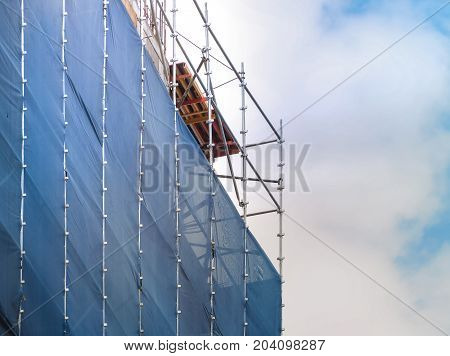 Steel scaffolding with canvas barrier dust for restoration of building, Outdoor image with place your text