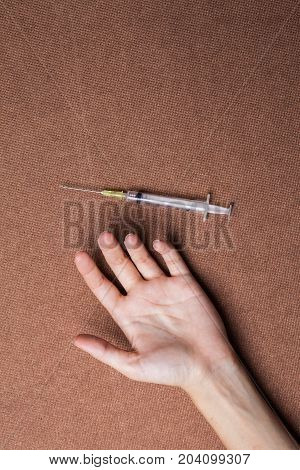 woman hand and drug Syringe on a dark background