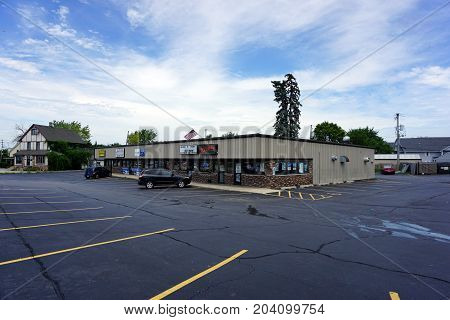 JOLIET, ILLINOIS / UNITED STATES - JULY 21, 2017: The Pine Tree Plaza, on Plainfield Road, includes Wolf's Fine Line Tattoo, the Computer and Phone Repair Center, and Zelmo's Bar and Grill.