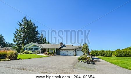 Wide asphalt driveway of residential house with three doors garage