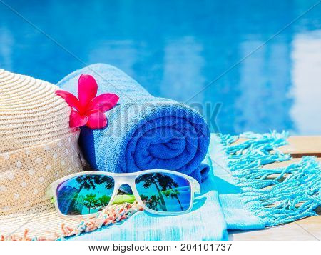 Red frangipani (plumeria) flowers sunglasses beach hat and blue towel at the side of swimming pool. Vacation beach summer travel concept