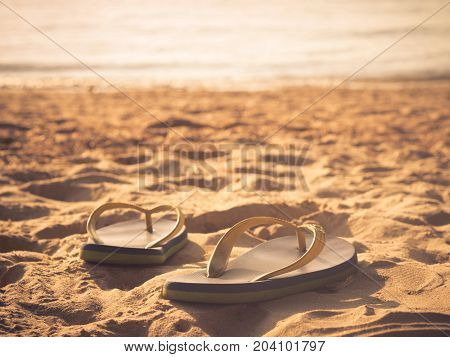 Soft focus at pair of flip-flops on the white sand beach with clear blue sea and skywarm and vintage tone. Sad and hopeless concept.
