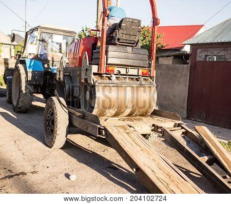heavy machine rolls a new asphalt road .