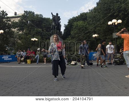 NEW YORK NEW YORK USA - AUGUST 25: Woman dancing in front of George Washington statue inside Union Square park and 14th street. Taken August 25 2017 in New York.