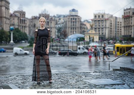 Blonde wooman dreesed in black dress in the city. Rainy day. Autumn in Kyiv