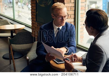 Financial analyst explaining diagram to coworker in cafe