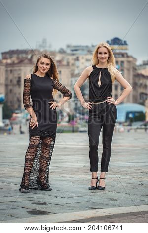 Two beautiful young women at Times Square in Kyiv. Rainy day. Autumn