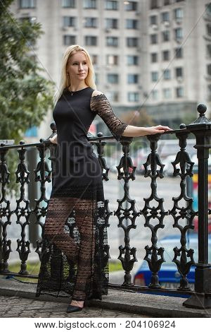 Blonde woman in a black long dress near forged fence. Autumn rainy day