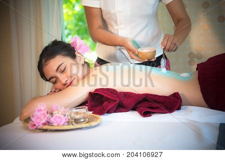 Masseur doing massage spa with treatment sugar srcup on Asian woman body in the Thai spa lifestyle so relax and luxury. Healthy Concept